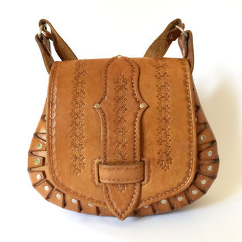 Vintage 1970s hand tooled tan leather saddle bag with buckle through front and riveted side panels