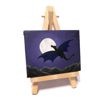 Mini Dragon in the Night Sky Painting - small acrylic art with a dragon silhouette flying in front of a full moon. Miniature canvas on easel