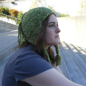 hand knit green hat with earflaps, tassel, and braids